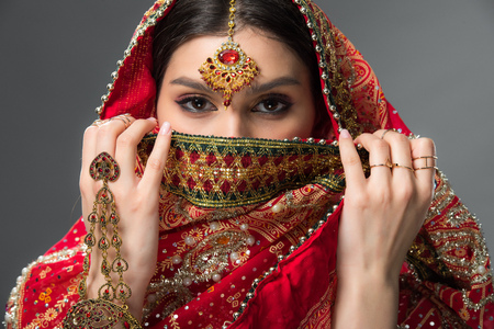 beautiful indian woman with bindi closing face, isolated on grey