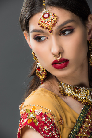 beautiful indian woman posing in traditional sari and bindi, isolated on grey Stock fotó