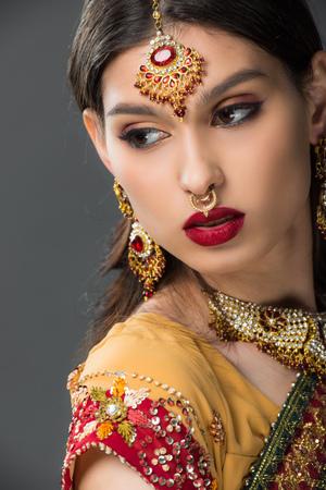 beautiful indian woman posing in traditional sari and bindi, isolated on grey Фото со стока