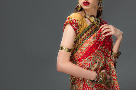 cropped view of indian woman posing in traditional sari and accessories, isolated on grey 版權商用圖片