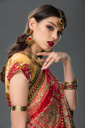 elegant indian woman posing in traditional sari and accessories, isolated on grey