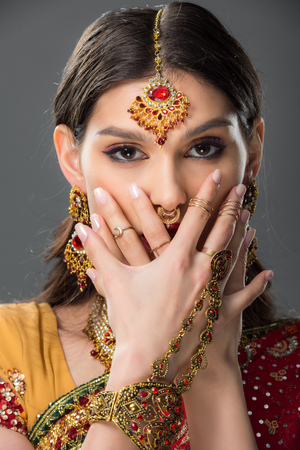 beautiful indian woman with bindi closing face with hands, isolated on grey Stock Photo - 117438456
