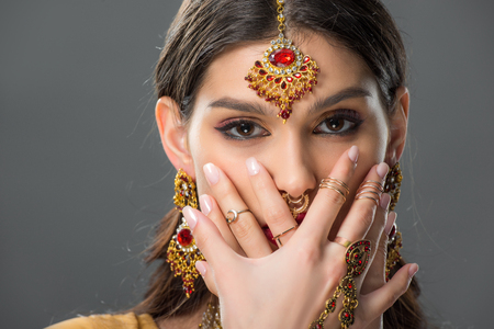 attractive indian woman with bindi closing face with hands, isolated on grey