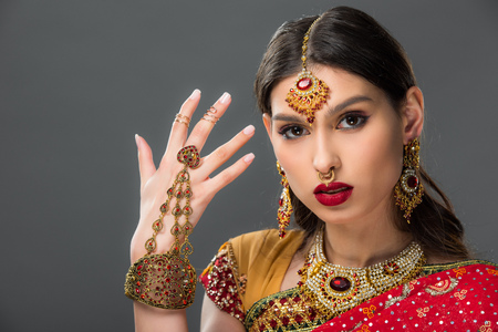 beautiful woman gesturing in traditional indian sari and accessories, isolated on grey Фото со стока