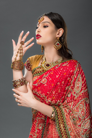 indian woman gesturing in traditional sari and accessories, isolated on grey