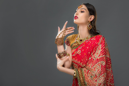 attractive indian woman gesturing in traditional sari and accessories, isolated on grey