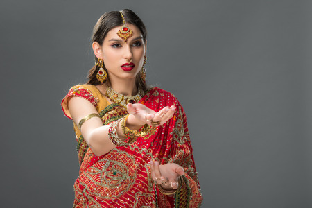 indian girl gesturing in traditional sari and accessories, isolated on grey