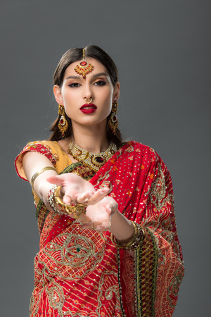elegant woman gesturing in traditional indian sari and accessories, isolated on grey