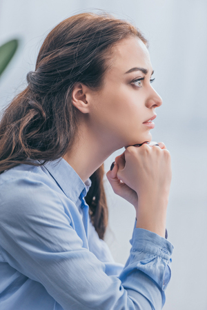 sad woman in blue blouse sitting and looking into distance at home, grieving disorder concept