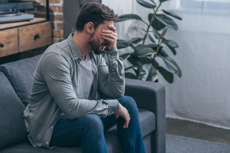 man sitting on couch and crying at home, grieving disorder concept 版權商用圖片