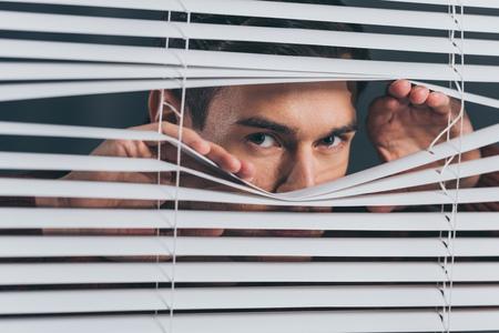 joven espiando y mirando a la cámara a través de las persianas Foto de archivo