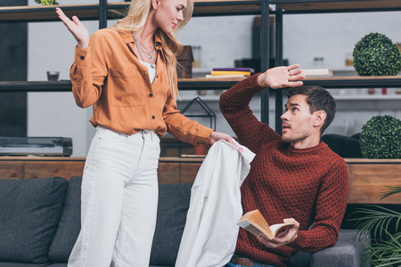 cropped shot of angry jealous woman showing male shirt with lips traces to scared man holding book at home