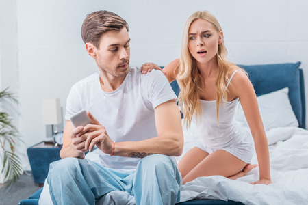 angry jealous woman looking at boyfriend using smartphone on bed, mistrust concept Banque d'images
