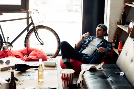 selective focus of man drinking beer from can and sitting on bean bag at messy home