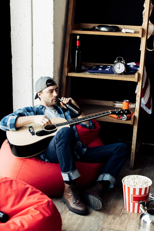 drunk man drinking beer and holding acoustic guitar at home
