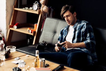 exhausted man playing video game in messy living room Standard-Bild