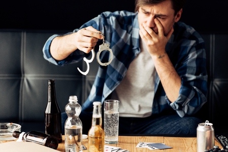 man covering face while looking at handcuffs after party Stock Photo