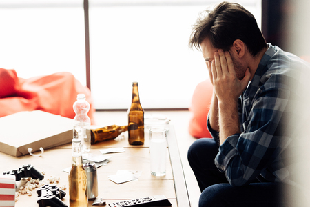 man covering face and suffering hangover after party