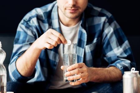 cropped view of man suffering from hangover holding aspirin and glass of water in hands