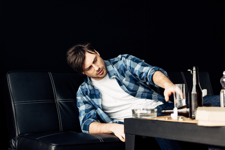 handsome man suffering from hangover taking glass of water from coffee table