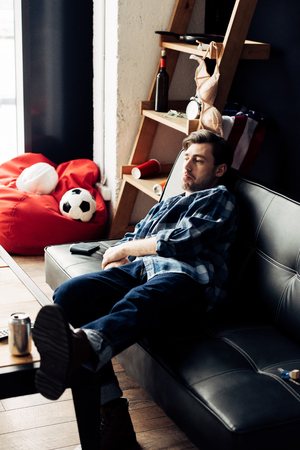 tired man lying on sofa after party at home