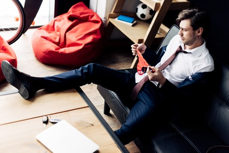 man in suit holding pink panties while sitting on sofa after party in office Stock Photo