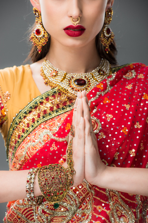 cropped view of indian woman in traditional clothing with namaste mudra, isolated on grey Imagens