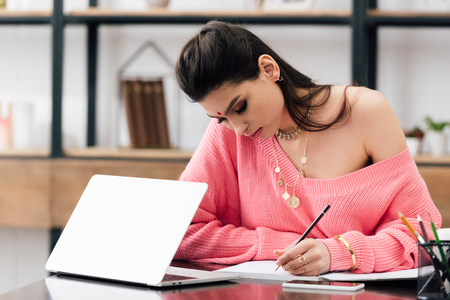 indian woman with bindi writing in notebook and studying with laptop at home Фото со стока - 117397341