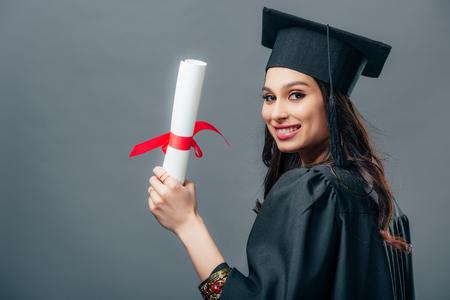 lächelnde indische Studentin in akademischem Gewand und Abschlusskappe mit Diplom, isoliert auf grau Standard-Bild