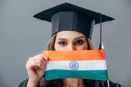 female indian woman in graduation cap holding indian flag, isolated on grey Stock Photo