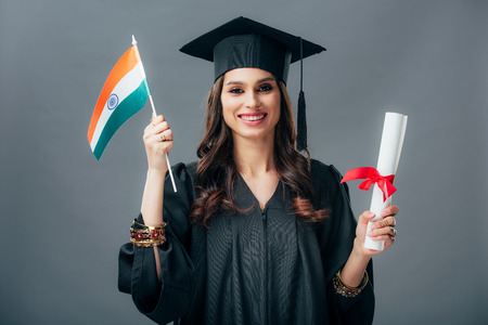 happy student in academic gown and graduation cap holding diploma and indian flag, isolated on grey 免版税图像