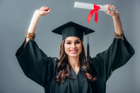 female indian student in academic gown and graduation hat celebrating with diploma, isolated on grey 写真素材