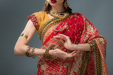 cropped view of attractive indian woman gesturing in traditional clothing, isolated on grey Stock fotó