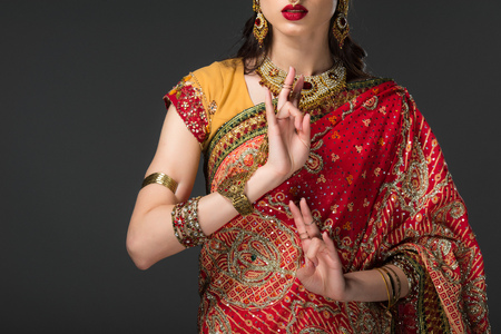 cropped view of indian woman in traditional clothing showing Window Wisdom Mudra, isolated on grey