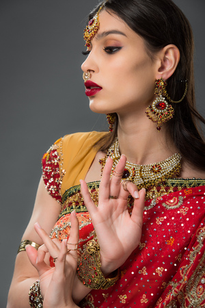 attractive indian woman in traditional clothing showing gyan mudra, isolated on grey