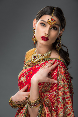 attractive indian woman posing in traditional clothing and bindi, isolated on grey