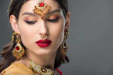 beautiful indian woman posing in traditional bindi, isolated on grey