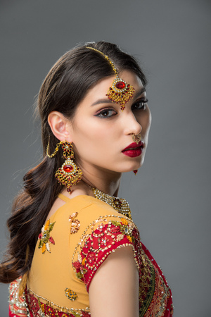 beautiful indian woman posing in traditional sari and accessories, isolated on grey Фото со стока