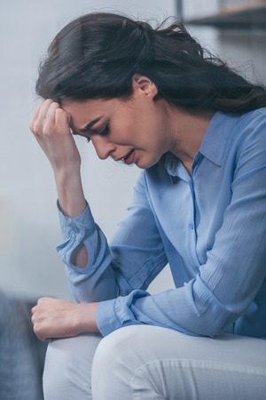 upset woman having headache, grieving and crying at home