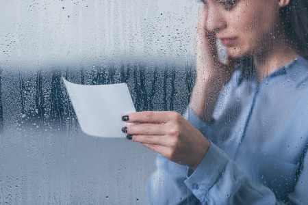cropped view of grieving woman holding photograph and crying through window with raindrops Imagens