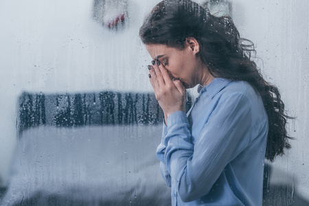 depressieve vrouw die gezicht bedekt met handen en thuis huilt door raam met regendruppels en kopieerruimte