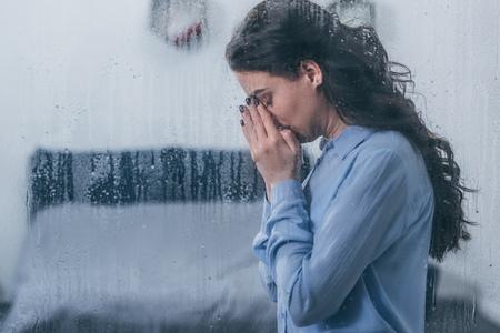 donna depressa che copre il viso con le mani e piange a casa attraverso la finestra con gocce di pioggia e copia spazio