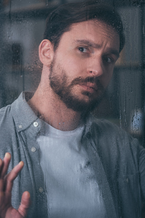 handsome upset man touching window with raindrops and looking away