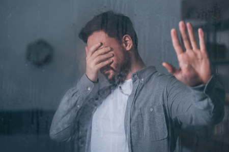 upset man covering face with hand, crying and touching window with raindrops