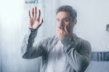 upset man covering mouth with hand and touching window with raindrops
