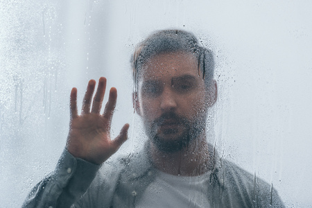 selective focus of raindrops on window with upset man on background