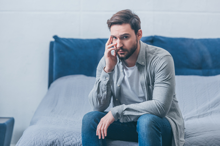depressed man sitting on bed, looking at camera and grieving at home Imagens