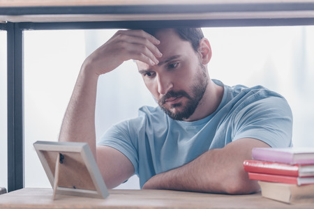 upset man touching head while looking at photo frame at home