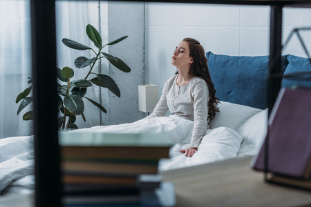 selective focus of sad woman lying in bed with eyes closed at home