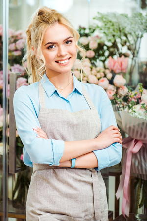 beautiful smiling female florist in apron looking at camera with flower shop on background